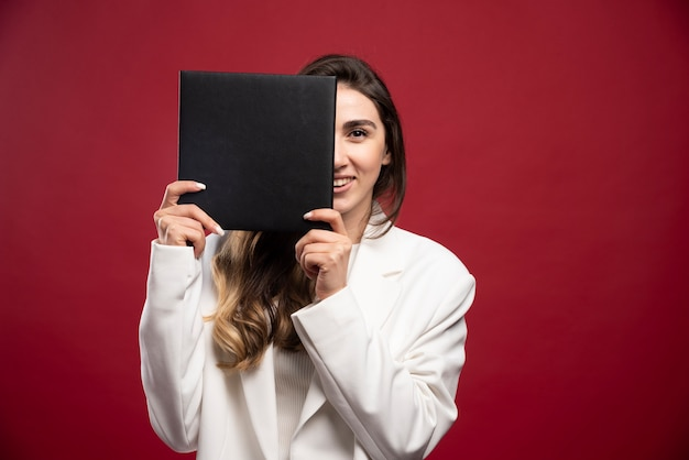 Donna d'affari che copre il viso con un taccuino