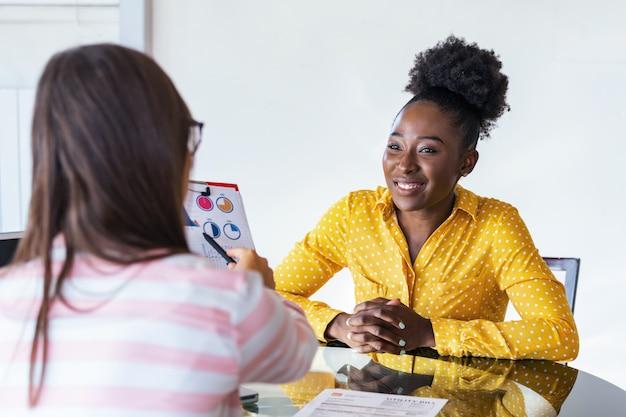 ビジネスの女性の同僚は、近代的なオフィスでビジネスアイデアを共有して話しているラップトップで働いています。