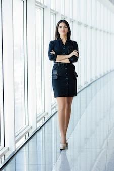 ビジネス女性は、パノラマの窓とオフィスで手の肖像画を交差させました。