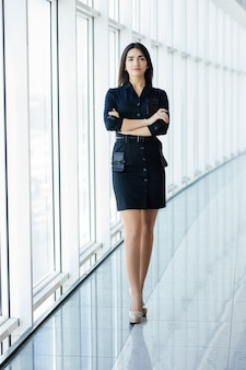 Business woman crossed hands portrait in office with panormic windows.