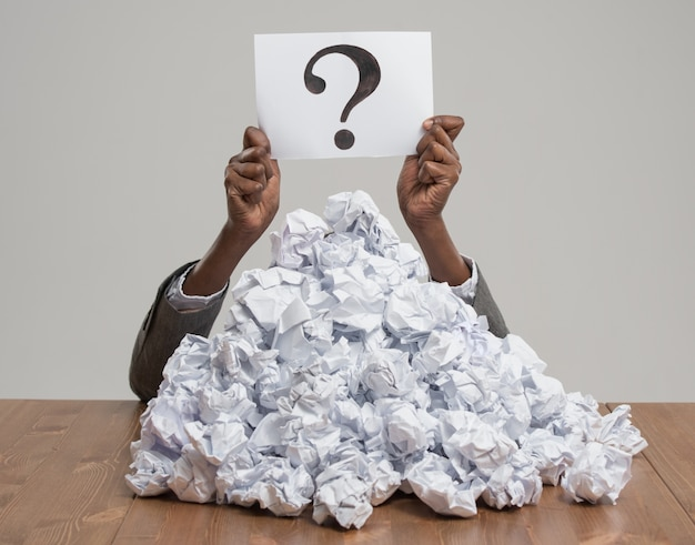 Business woman under crumpled pile of papers