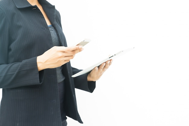 Business woman in dark suit using her tablet and mobile phone on white background with copy space