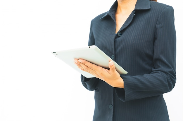 Business woman in dark suit using her tablet on white background with copy space