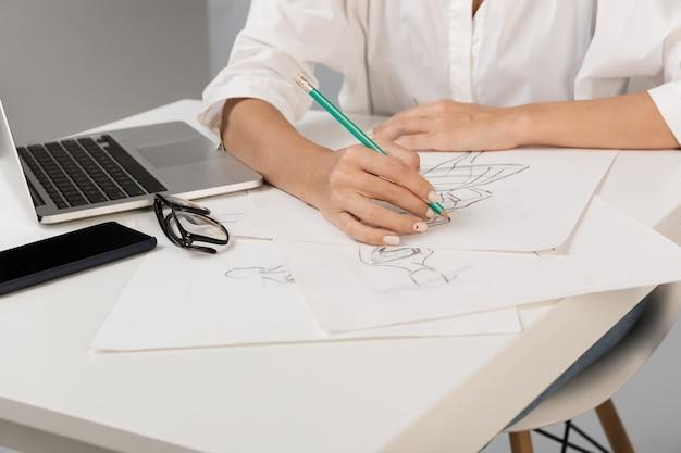 Дизайнер бизнес-леди, изолированные на серой стене, сидя за столом, рисунок