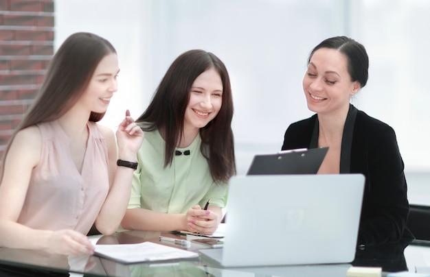 Деловая женщина обсуждает документ с сотрудницей, когда они делят стол в офисе