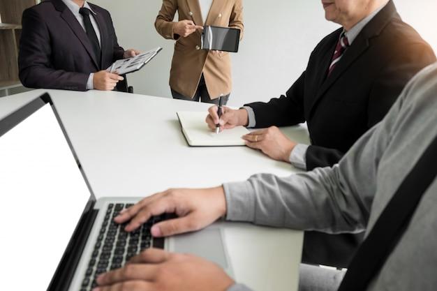 ビジネスの女性は、企業の訓練のクラスを周りの若いビジネスマンのグループに与えるタッチパッドで財務チャートを議論する