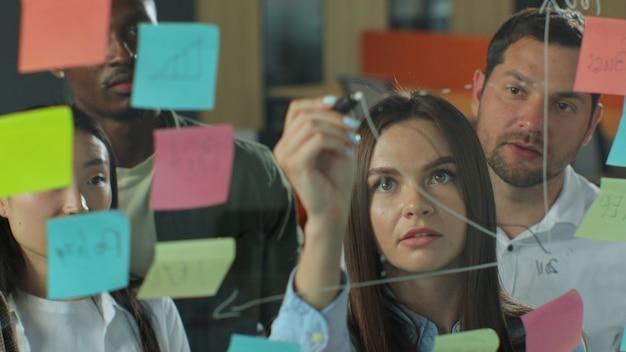 Деловая женщина рисует график на стеклянной стене с наклейками, молодая бизнес-команда проводит мозговой штурм, коллеги одобряют концепцию успеха в бизнесе
