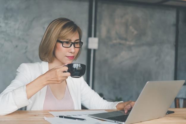 Деловая женщина пьет кофе и работает на ноутбуке, ищет в интернете, просматривает информацию, сидя и работая за столом