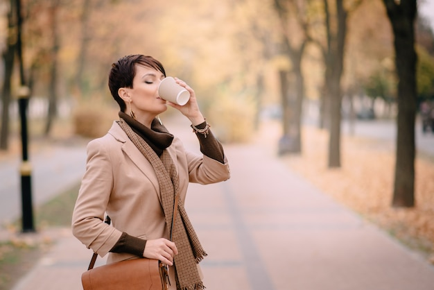 Business woman drinking coffee in autumn street