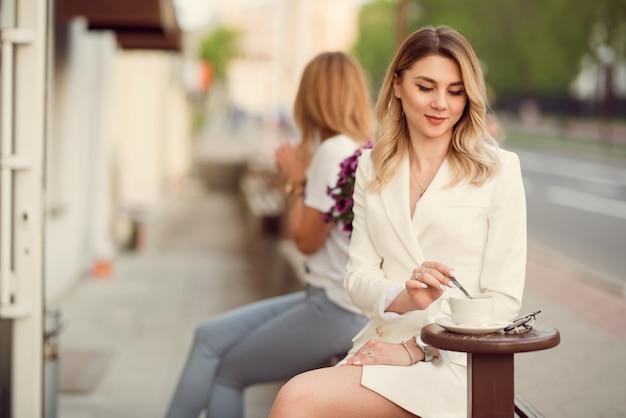Деловая женщина пьет кофе на улице