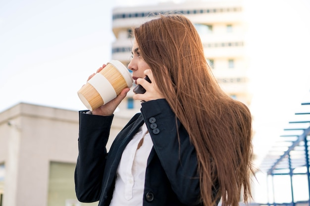 Business woman drinking coffee  talking on the phone young entrepreneur woman at her workplace