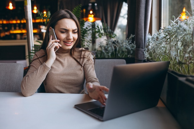 Business woman drinking coffee and working on laptop in a cafe