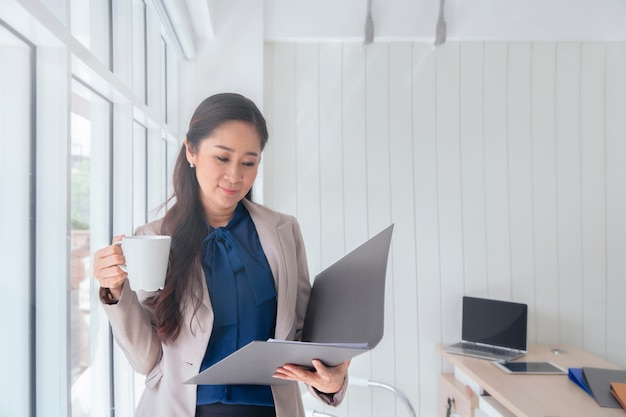 Business woman drinking cup of coffee and standing at a window in office