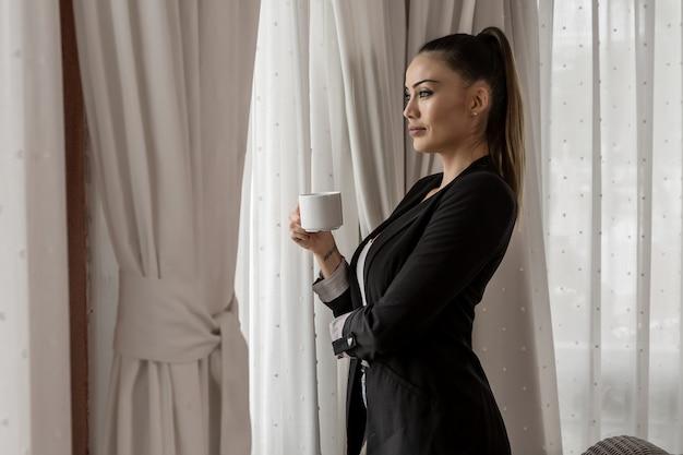 Business woman drinking tea in hotel