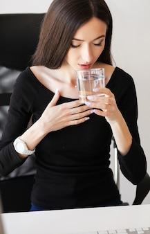 Деловая женщина пьет воду и принимает лекарства