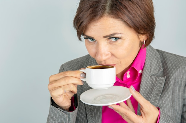 Business woman drinks coffee from a white cup close-up