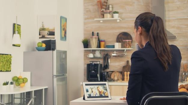 아침 식사를 하면서 여동생과 화상 통화를 하는 동안 비즈니스 우먼. 최신 온라인 인터넷 웹 기술을 사용하여 웹캠 화상 회의 앱을 통해 친척, 가족, 친구 및 동료와 채팅