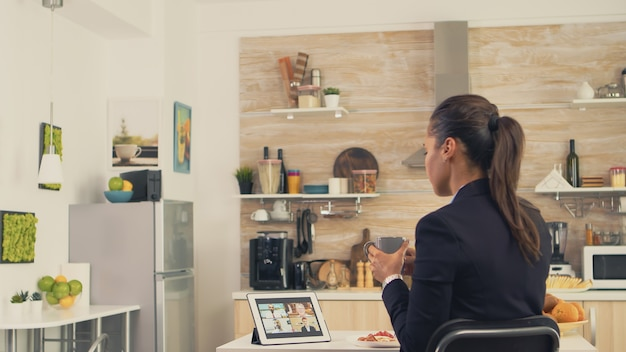 Business woman during a video call with friends while eating breakfast before leaving to the office. using modern online internet web technology to chat via webcam videoconference app with relatives,