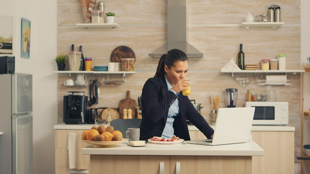 朝食を食べてラップトップに取り組んでいるビジネスウーマン。朝の集中ビジネスウーマンがオフィスに行く前にキッチンでマルチタスク、ストレスの多い生き方、キャリア、そして目標を達成する