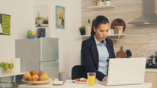 Donna d'affari che mangia pane tostato con burro mentre lavora al computer portatile durante la colazione. donna d'affari concentrata al mattino multitasking in cucina prima di andare in ufficio, stressante w