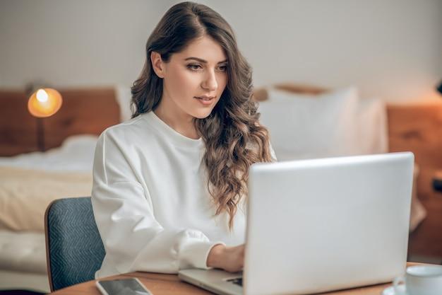 ビジネスウーマン。テーブルに座ってラップトップで作業しているエレガントな若い女性