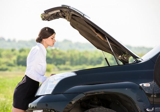 Business woman examining broken down car.