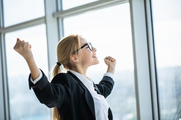 La donna di affari eccitata si tiene per mano sulle braccia alzate celebra la vittoria in ufficio moderno