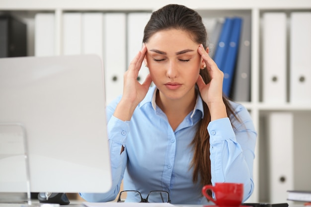 Business woman experiencing stress in the workplace, holding her hand behind her head