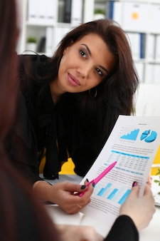 Business woman explaining financial chart to collegue
