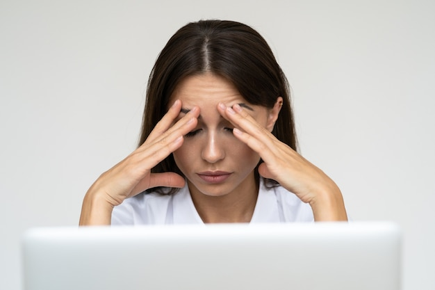 Business woman feeling headache from work on laptop