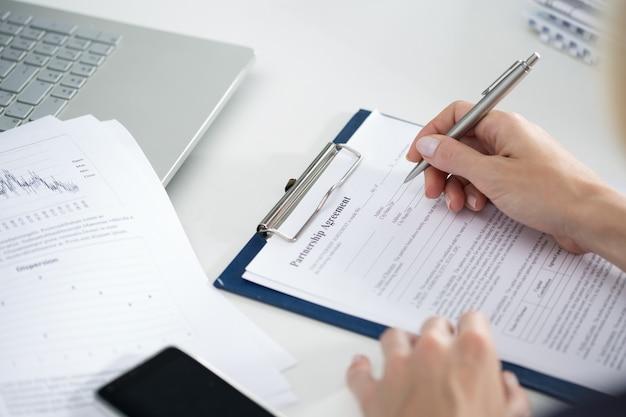 Бизнес-леди заполняя соглашение о партнерстве пустым. концепция бизнеса и партнерства