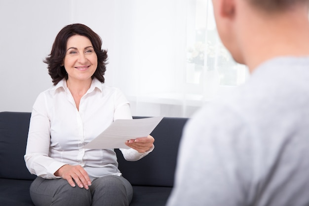 Business woman giving document or contract to her colleague in office