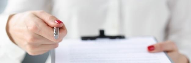 Деловая женщина дает документ в буфер обмена для подписи крупным планом заключения контракта