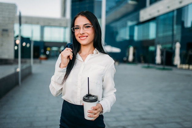 Business woman in glasses, suit and coffee in hand. modern building, financial center, cityscape.