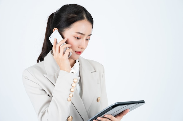 Business woman in grey suit using phone and tablet to connect with customers.