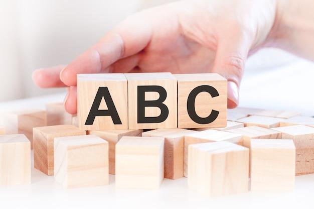 비즈니스 우먼 손 abc 단어로 나무 큐브 블록을 변경합니다. 재무, 관리, 교육, 비즈니스 및 경제 개념
