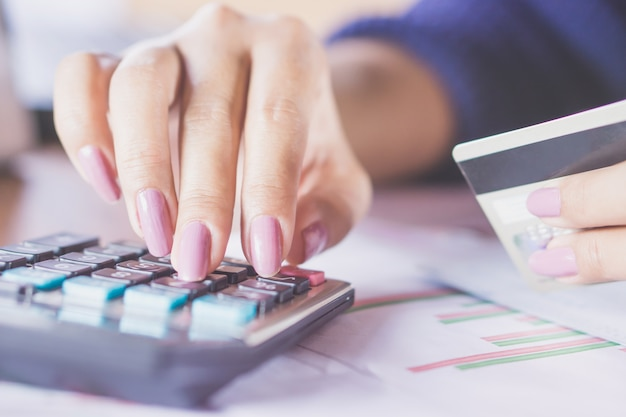 Business woman hand counting on calculator using credit card