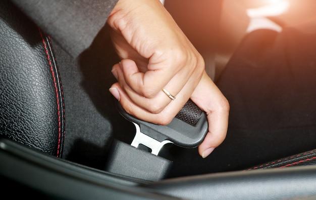ビジネスの女性の手がシートベルトを締めます。