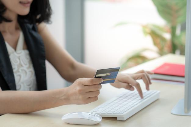ビジネスウーマンの手はラップトップコンピューターでオンラインショッピングインターネットにクレジットカードを保持します