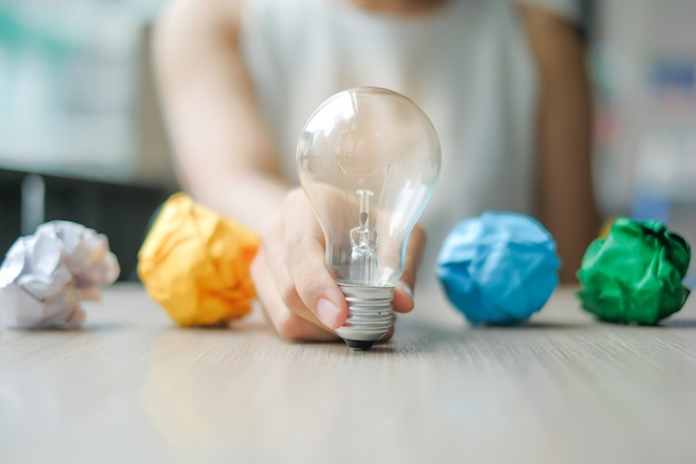 Business woman hand holding light bulb or lamp with colorful crumpled paper