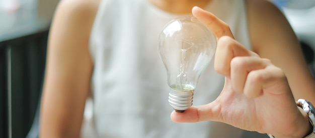 Business woman hand holding light bulb or lamp.