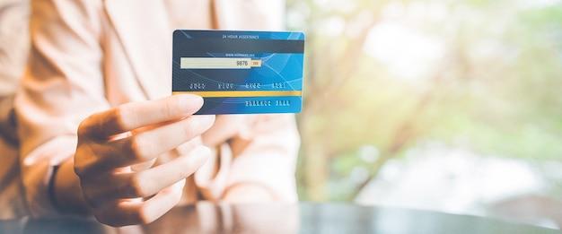 비즈니스 여성 손은 구매를 위해 파란색 신용 카드를 보유하고 있습니다. 웹 배너의 경우.