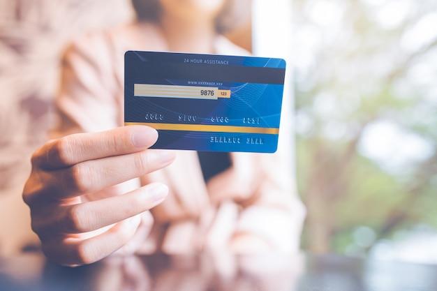 비즈니스 여자 손에는 파란색 신용 카드가 있습니다.