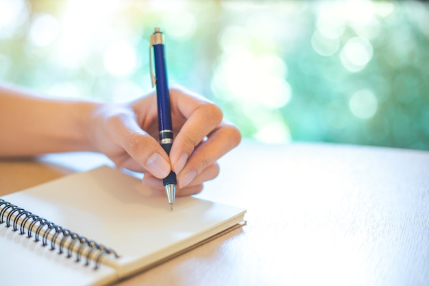 Business woman hand is writing on a note pad with a pen in office.