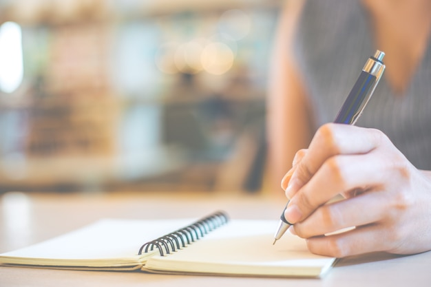Business woman hand is writing on a notepad
