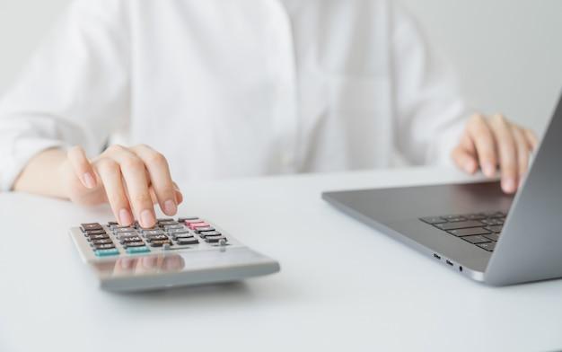 비즈니스 여자 손 프레스 계산기 및 사무실 집에 테이블에 월별 비용을 계산합니다.