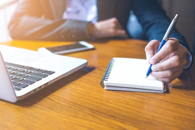 コンピュータのラップトップを使用して、オフィスでペンでメモ帳に書くビジネス女性の手