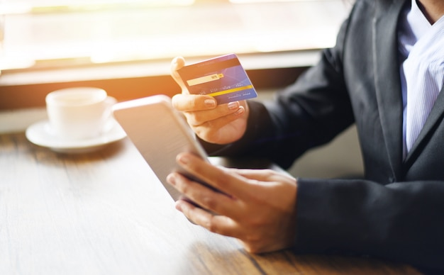 Business woman hands holding credit card and using smartphone for shopping online people paying technology
