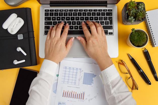 Business woman hands typing on laptop and woring with reports top view over yellow office desk