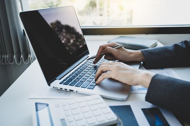 Деловая женщина руки с помощью ноутбука анализирует график